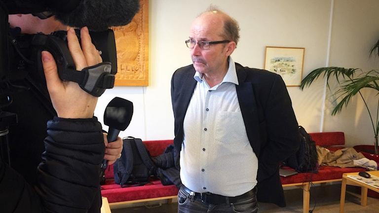 En bild på åklagare christer sammens i en ljus skjorta och en mörk kostymjacka och jeans. i bakkgrunden syns en röd soffgrupp, en tavla och en grön växt. han har mustache och stålbågade glasögon. till vänster står en kameraperson och intervjuar honom.