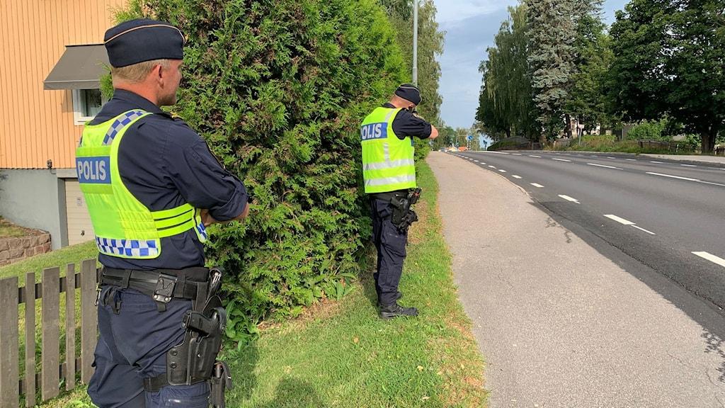 Två poliser i uniform och varselväst som står vid vägen och genomför en hastighetetskontroll.