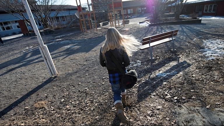 En ensam flicka går över en skolgård med skolväskan på axeln. Det är vinter men ingen snö.