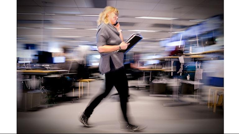 En kvinna går igenom ett öppet kontorslandskap med en pärm i famnen och en telefon tryckt mot örat.