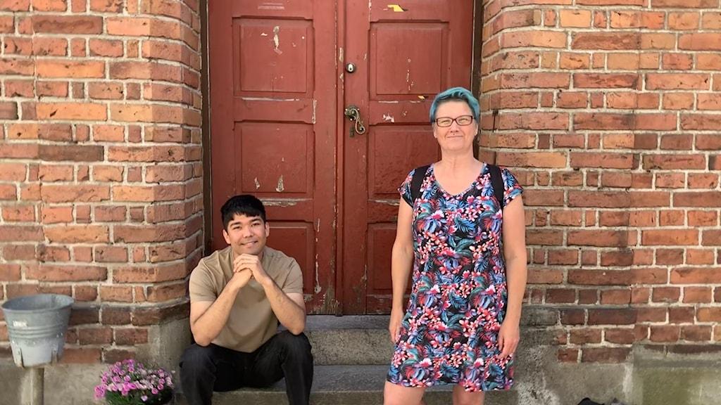 En man sitter ner på en trappa till en port, en kvinna som står upp bredvid.