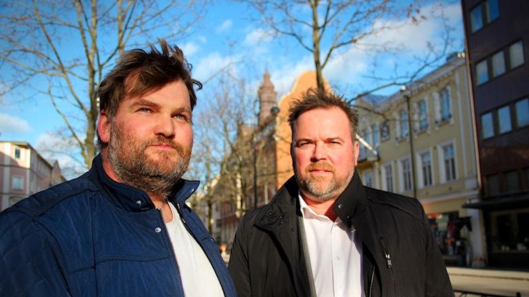 Anders Jansson och Karl Bertil Johansson står i solen på Nygatan i Gävle. Himlen bakom är blå. De bär en blå respektive en svart jacka och en vit tröja under. Båda har skägg och mörkt hår. De ser bekymrade ut.