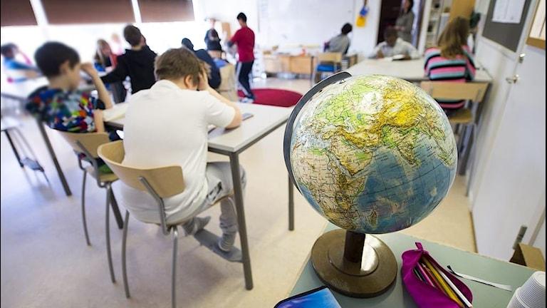 En bild på ett klassrum med fjärdeklassare som har tyst lässtund. I förgrunden syns färgglada pennskrin i ceriserosa och blått och en jordglob. Elever sitterpå stolar i bakgrunden. Deras ansikten syns inte. Bilden är en arkivbild.