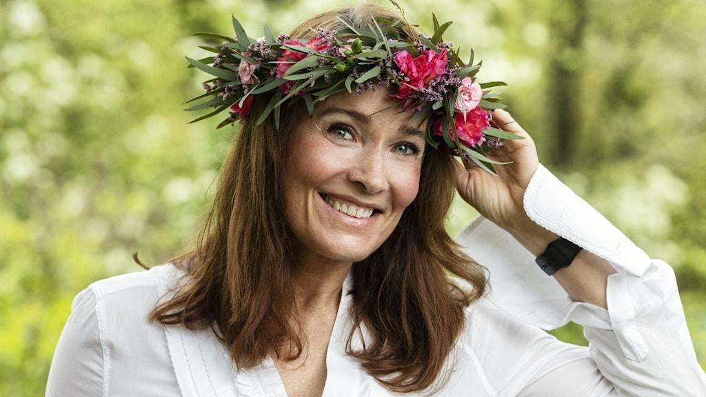 Agneta Sjödin i blomsterkrans med ena handen på kransen och den andra vilande mot ett träd.