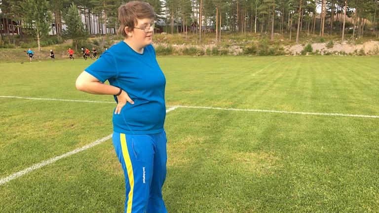 Jessica en tjej i blåa träningskläder, kort hår och glasögon står på fotbollsplanen.