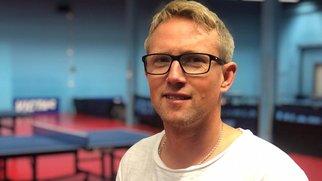 SUIF:s tränare Fredrik Lundquist står framför några pingisbord inomhus.