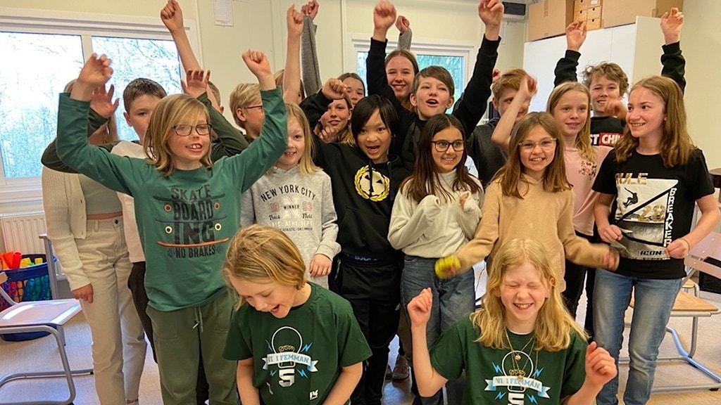 En klass med barn i årskurs fem som jublar med händerna mot taket.
