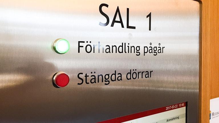 """En tavla i borstat stål med texten """"Sal 1"""" i stora bokstäver längst upp. Längre ned är en rad med """"Föhandling pågår"""" med en grön, lysande lamap framför. Under står """"stängda dörrar"""" med en röd lmapa framför, men den är släckt."""