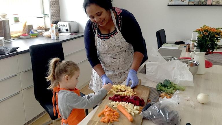 Sofia hjälper Shashi att lägga den tänade potatisen i en kastrull. Potatisen förkokas innan stekning.