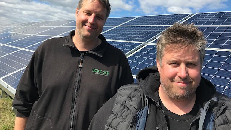 Bröderna Emil och Henrik Brink står framför solcellspaneler på Hudiksvalls flygfält.