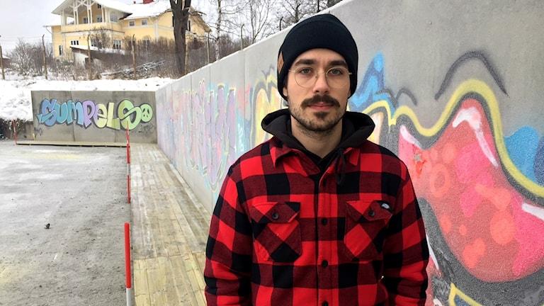 Konstnären David Larsson framför graffitiväggen
