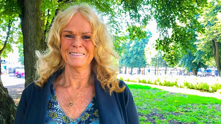 Ett porträtt på Ulla Maria Andersson i en park vid ett träd. Det grönskar runt om. Hon har ett litet guldhalsband och ler.