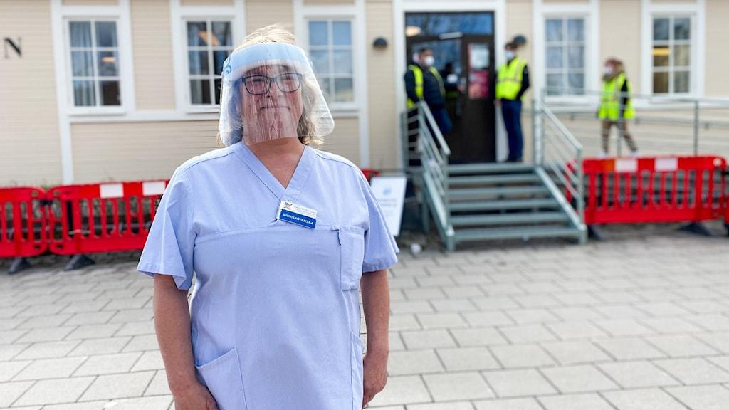 En kvinna med visir står framför en byggnad.