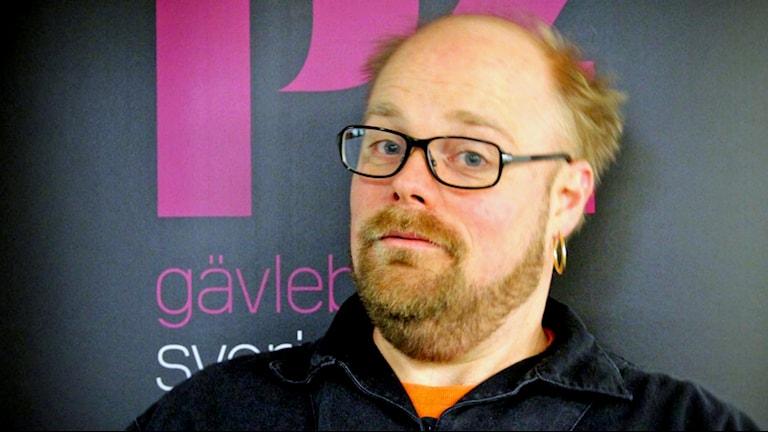 Niklas Folkegård, P4 Gävleborgs länskorrespondent, framför P4 Gävleborg- loggan.