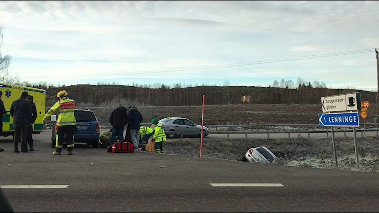 En bil ligger i diket och flera räddningtjänstpersonal står vid en annan bil och hjälper till
