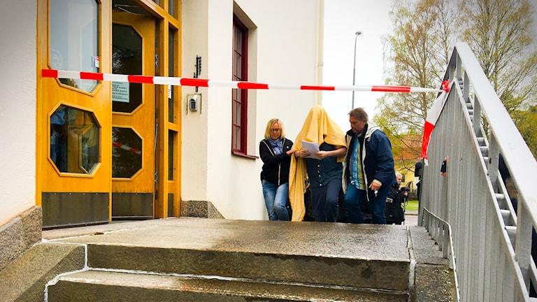 Den misstänkte kommer till tingshuset i hudiskvall med två ledsagare och en ljusgul filt över huvud och axlar