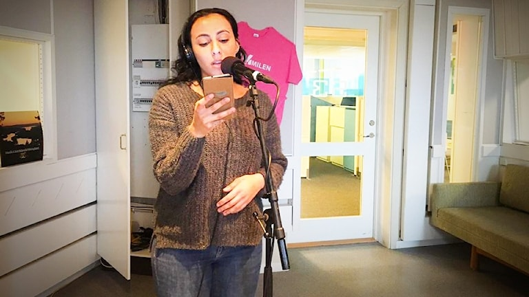Sabina Jarrar sjunger i en mikrofon på stativ i studion samtidigt som hon håller upp sin mobil med texten som hon läser. Hon bär en brun/grå stickad tröja och blå jeans.