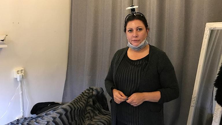 Emilia Sjöholm står med ansiktsmask i sin fransstudio