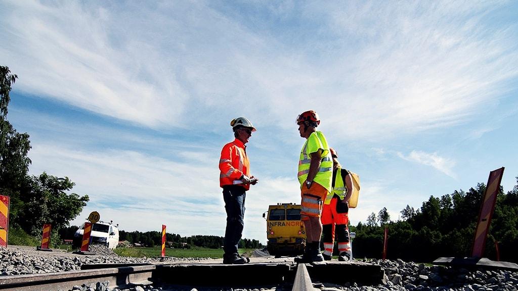 Tre personer står och pratar på ett järnvägsspår i bakgrunden en gul maskin.