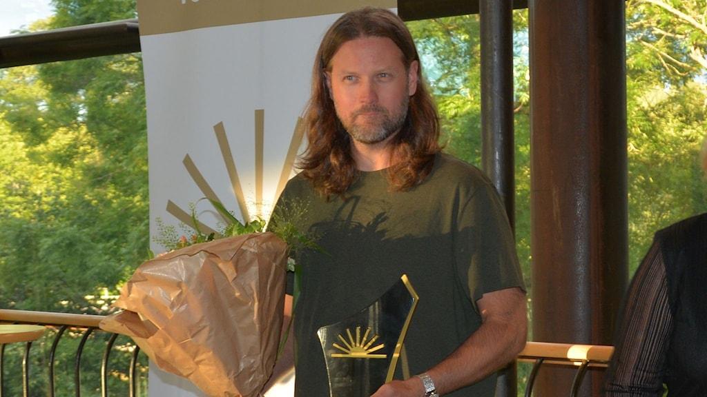 Man som har vunnit Årets Företagare i Gävleborg står med sitt pris och blommor.