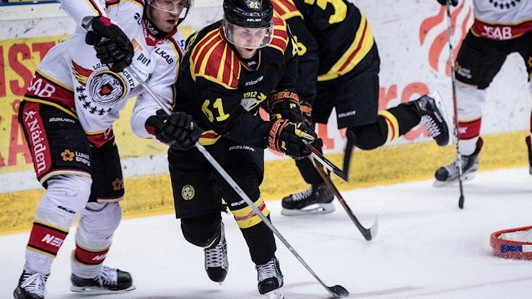 Två hockeyspelare försöker komma först till pucken.