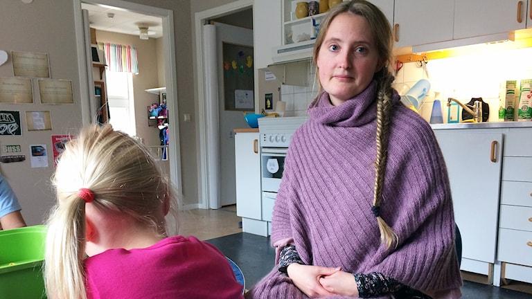 Kvinna med långt ljus hår i fläta lila tröja bredvid ett barn bakifrån.