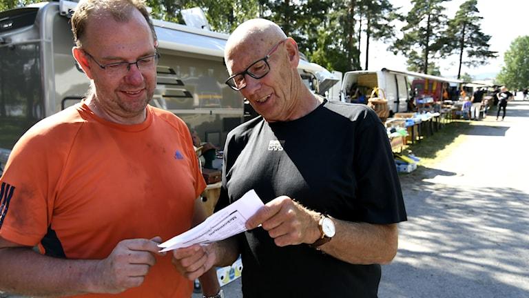Två män som tittar i ett papper. I bakgrunden marknadsstånd.