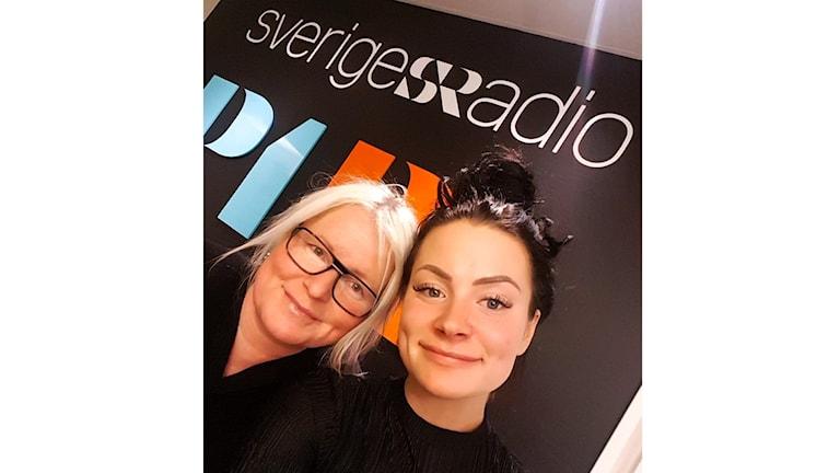 Anna och Felicia Eriksson, mor och dotter från Sandviken tar en selfie framför Sveriges radio - väggen. Anna har ljust blond hår och svarta glasögon och felicia har mörkbrunt hår uppsatt i en knut.