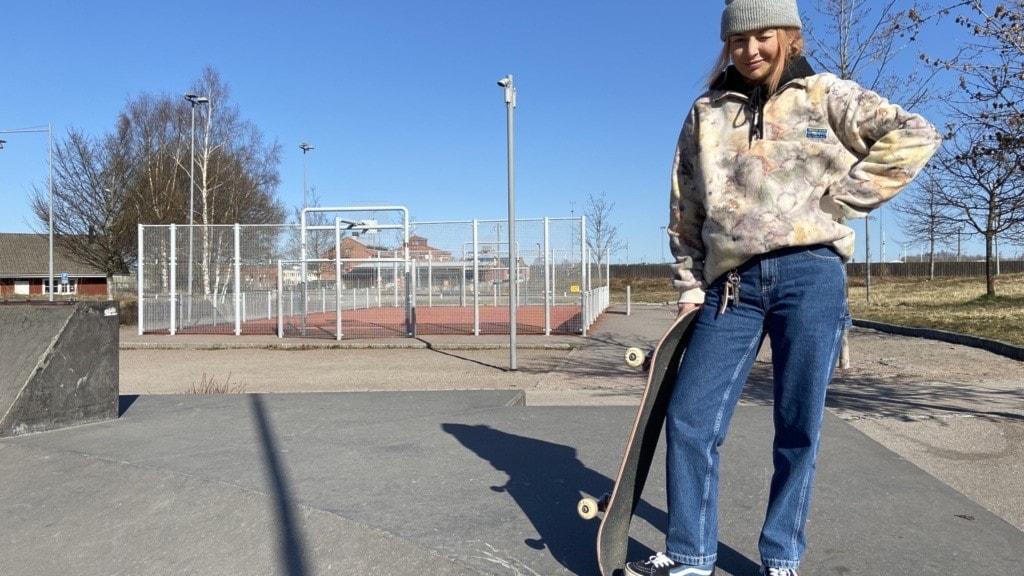 Kvinna som lutar sig mot en skateboard. Står i en skatepark.