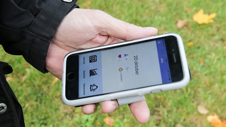 En hand som håller i smartphone som visar appen.