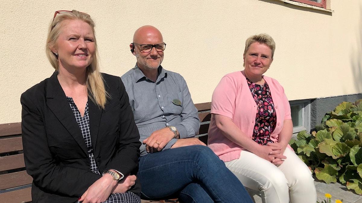 Socialchef Kristina berglund, Nils-Olof Nilsson, chef för individ- och familjeomsorgen och Bente Sandström, chef för arbetsmarknad- och flyktingenheten i Nordanstig sitter på en bänk utanför kommunkontoret i Bergsjö.