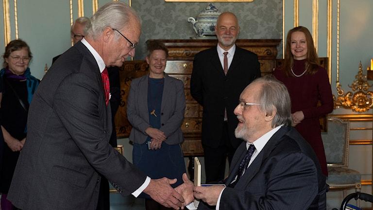 Carl Gustaf delar ut Prins Eugen-medaljen till målaren Mårten Andersson vid en ceremoni på Stockholm slott i november 2015.