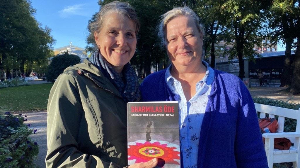 Två kvinnor håller upp en bok