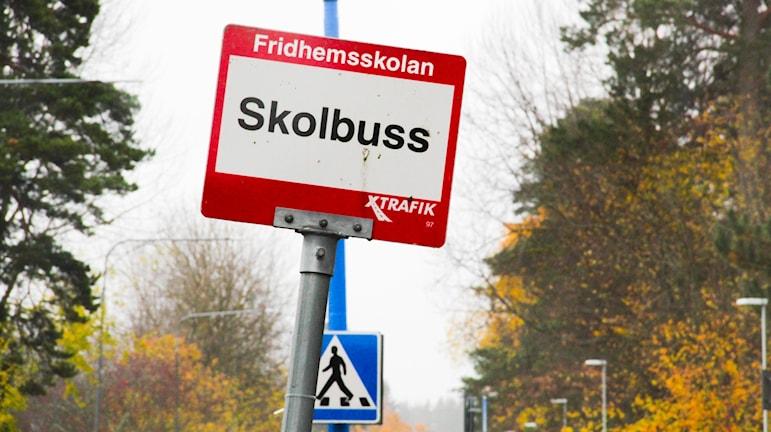 En skylt med texten fridhemsskolan: busshållplats. Det är höst och regnigt och mulet i bakgrunden.