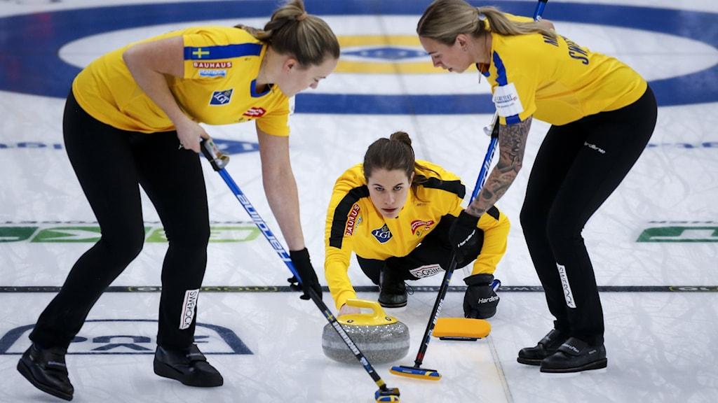 Tre damer tävlar i curling.