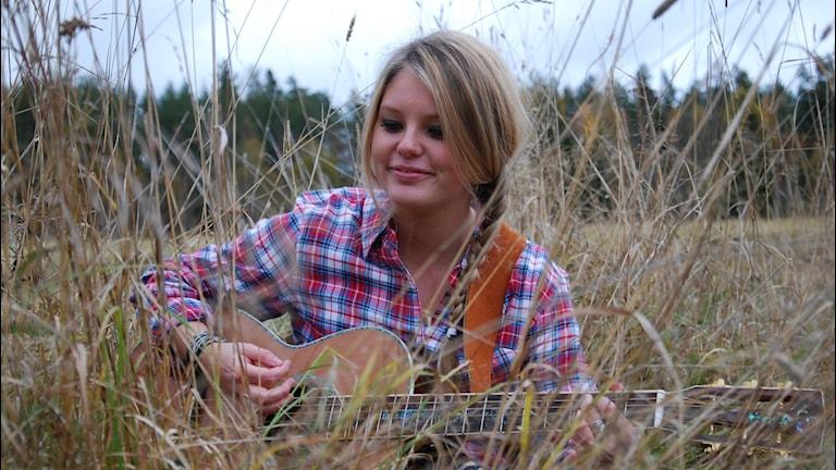 Jessica Bohlin i en rutig skjorta med en gitarr i en äng med högt gräs