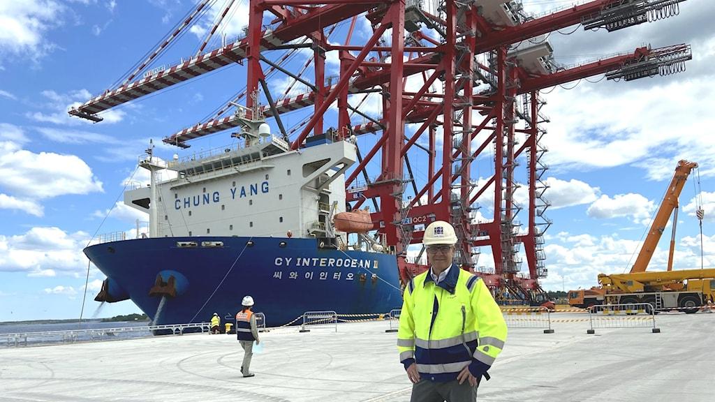 En man i skyddsutrustning står framför tre nya kranar i en hamn.