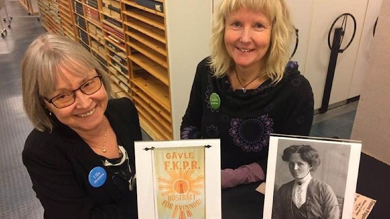 Arkivchefen Ulla Ejemar och arkivpedagogen Camilla Larsson vid Gerda Modéns porträtt.