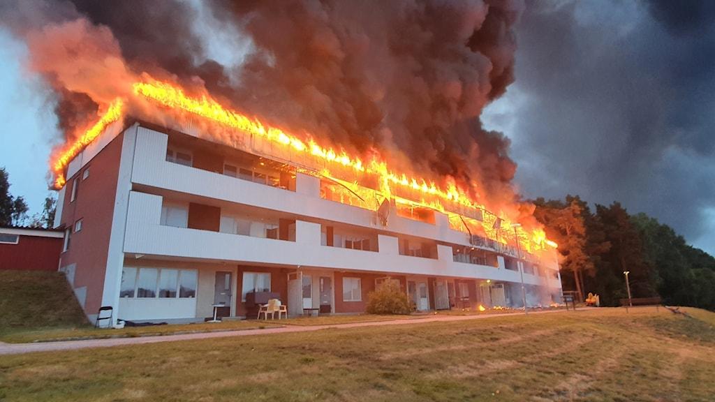 Ett brinnande hus med fullt utvecklad brand på vinden.