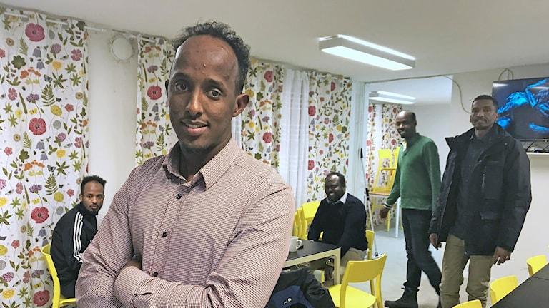 Glad man med somaliskt ursprung i en kvarterslokal framför andra män.