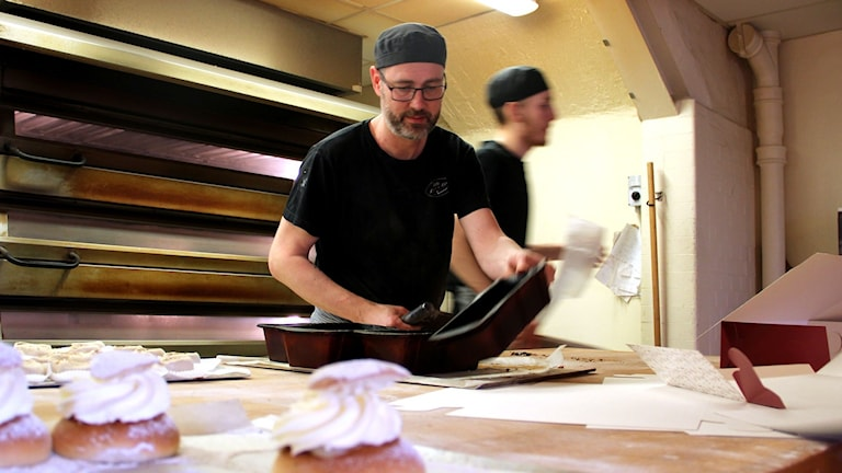 Bagaren Mats Harich vid bakbordet med tre semlor på en plåt i förgrunden och en ugn i bakgrunden.