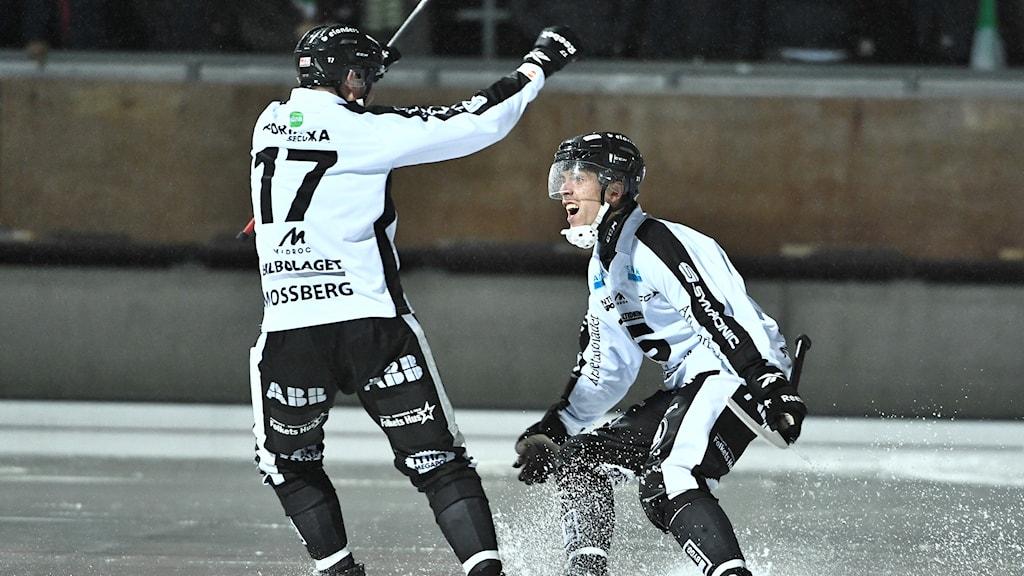 Två spelare från Sandviken är glada över bandymatchen.