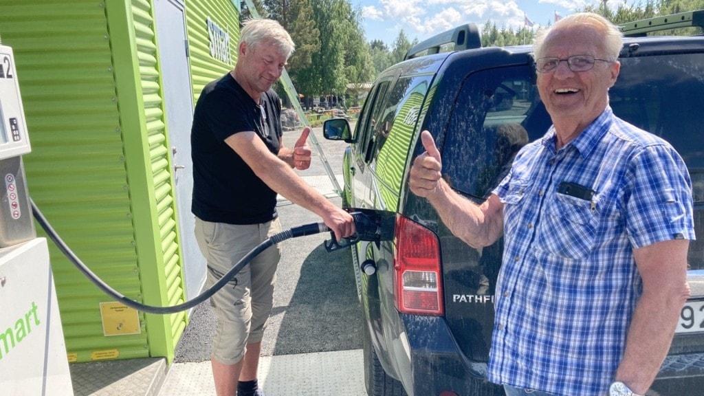 Två män gör tummen upp vid en bensintank.