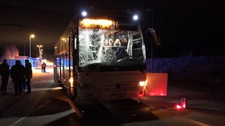 En buss i mörker med krossad framruta.