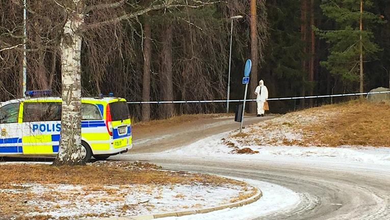 En tekniker, helt klädd i vitt inklusive vit huva, kommer gående ut från ett skogsområde som är avspärrat med polisband. Hen håller vad som ser ut som en brun papperspåse i ena handen. I förgrunden suns vändplanen och en polispiket.