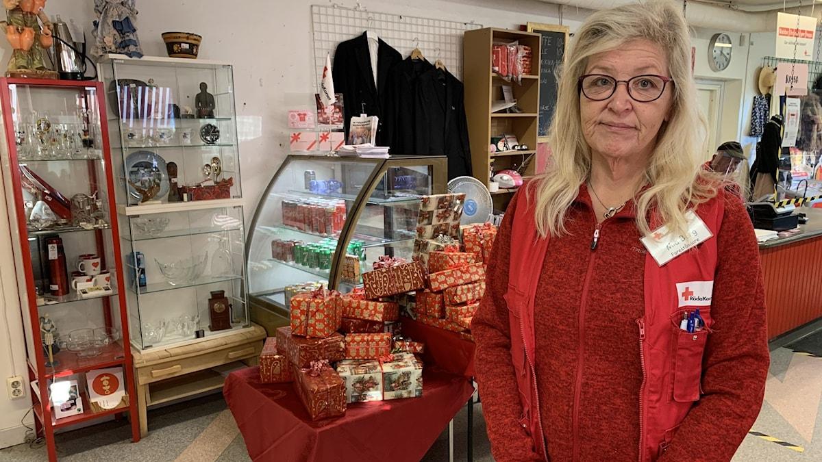 Kvinna i röda kläder, bär glasögon i bakgrunden finns en hög med julklappar och en kyldisk.