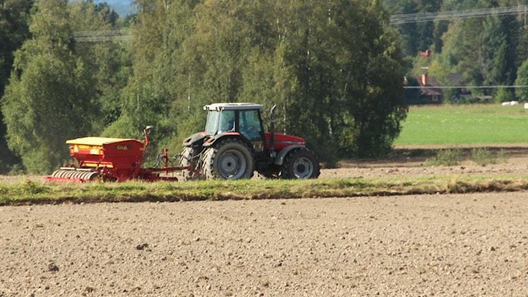 Traktor som kör på en åker.