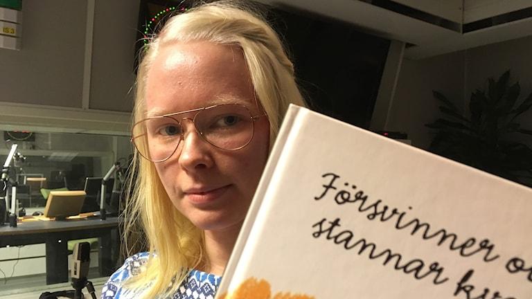 """Jenny Eriksson håller i sin bok """"Försvinner och stannar kvar"""""""