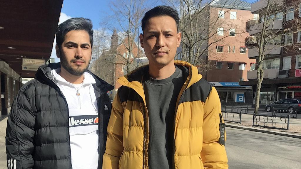 Två killar med mörkt kort hår utomhus.