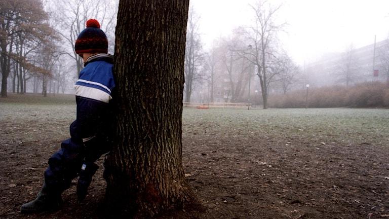 Barns om lutar sig mot träd, ensam